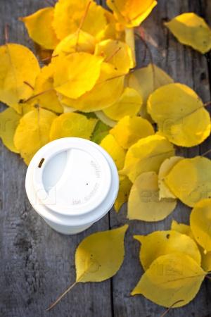 Чашка кофе и желтые осенние листья на старом деревянном столе