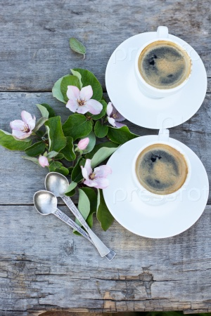 Кофе и весенние цветы на фоне старых деревянных досок на солнце