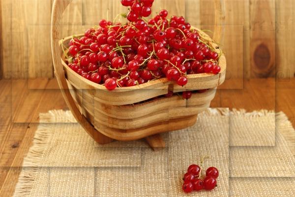 Свежая красная смородина в деревянной вазе