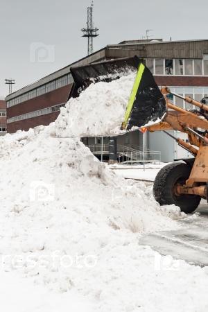 Трактор сгребает снег зимой на улице