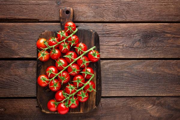 Свежие помидоры черри на веточках на деревянном столе