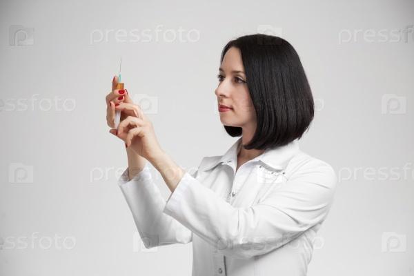 Молодая красивая женщина-врач со шприцем