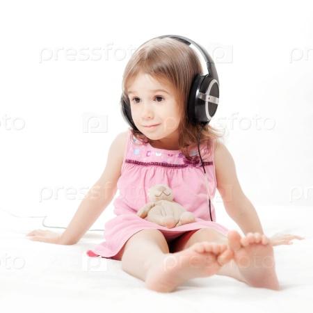 Маленькая девочка слушает музыку