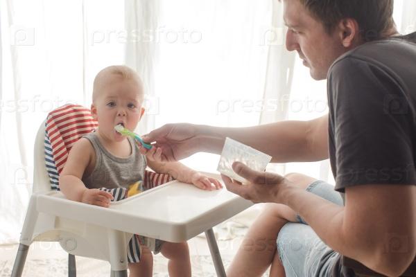 Отец кормит младенца