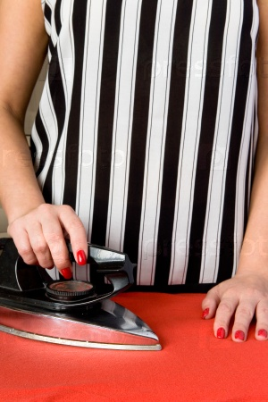 Женские руки со старым электрическим утюгом
