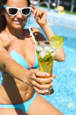 Девушка с коктейлем у бассейна