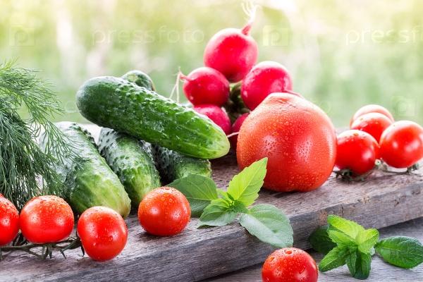 Свежие овощи на деревянный стол в саду