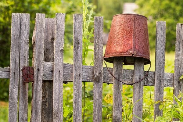 Старое ржавое ведро на деревянный заборе