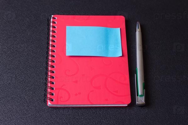 Красный блокнот на спирали с наклейкой и ручка