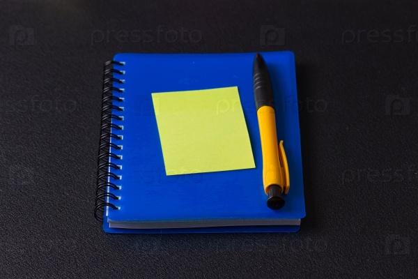 Синий блокнот с разноцветными наклейками и ручкой