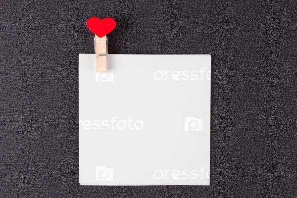 Лист бумаги на прищепке с красным сердцем