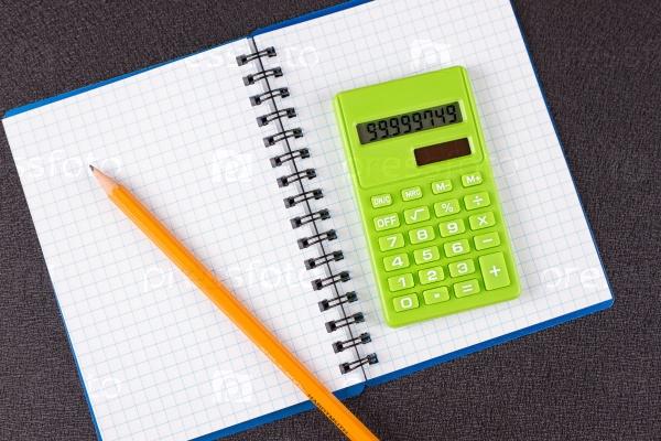 Калькулятор и карандаш на фоне блокнота