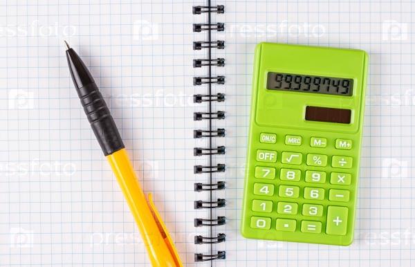 Калькулятор и ручка на фоне блокнота