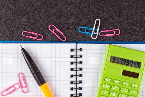 Калькулятор и ручка на блокноте