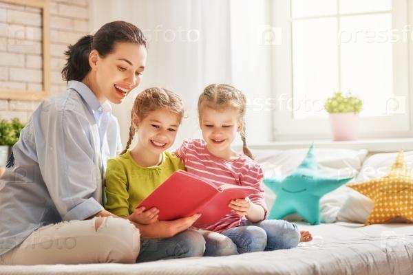 Мама читает книгу дочерям