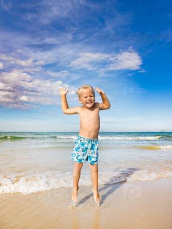 Мальчик прыгает на пляже