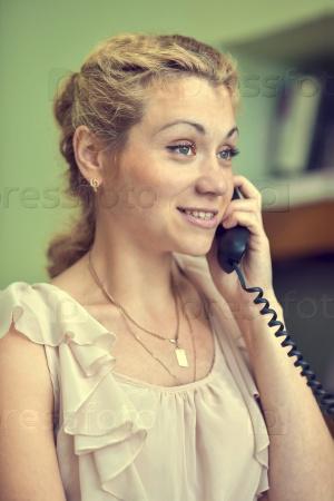 Девушка разговаривает по городскому телефону