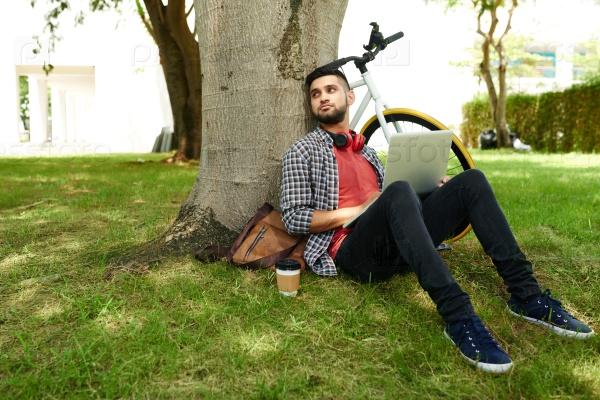 Счастливый мужчина с ноутбуком в парке
