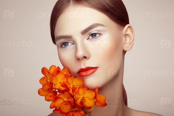 Портрет красивой молодой женщины с орхидеей