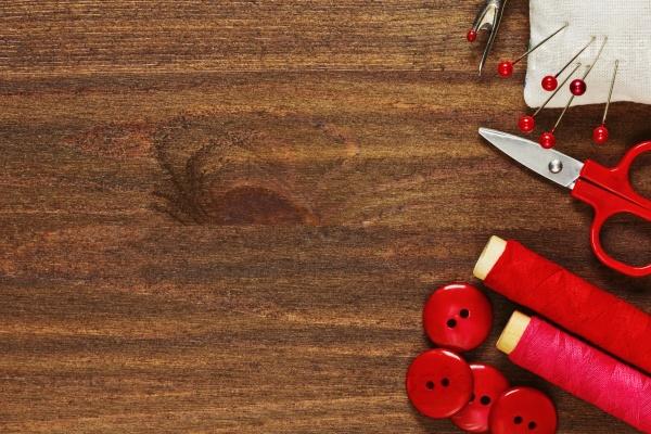 Швейные инструменты в оттенках красного на деревянном столе