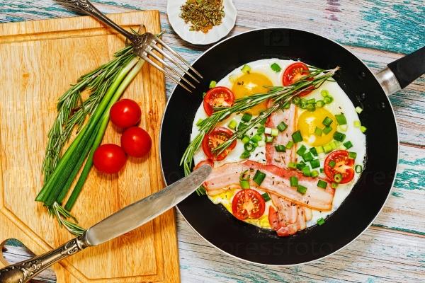 Жареные яйца с беконом, помидорами и зеленью
