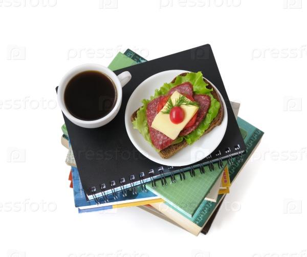 Стопка книг и тетрадей с чашкой кофе и бутербродом