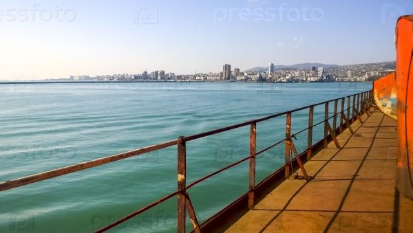 Вид на море и городской пляж с набережной порта