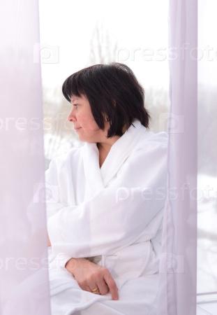 Женщина средних лет у окна