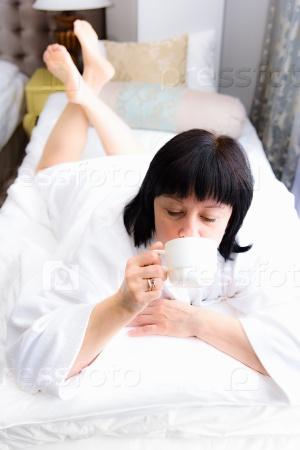 Женщина утром в постели с чашкой кофе