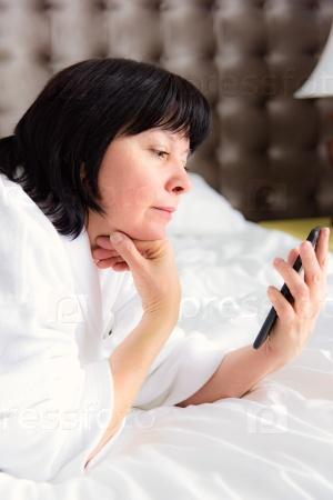 Женщина с телефоном в постели