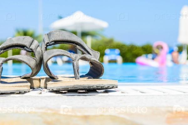 Кожаные сандалии на краю бассейна