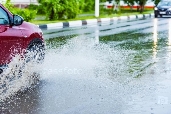 Автомобиль в дождь едет по луже