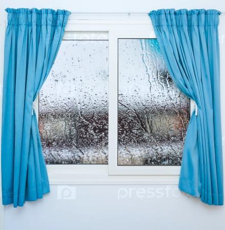 Закрытое окно с занавесками в дождливый день