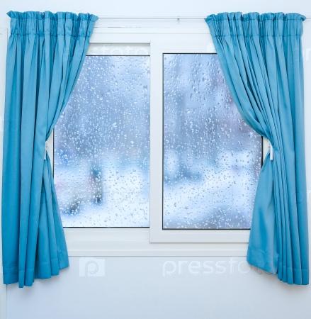 Закрытое окно с занавесками в дождливую погоду
