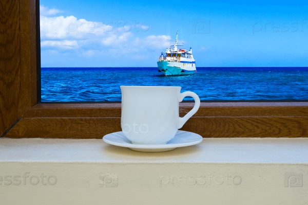 Чашка кофе у окна с видом на море