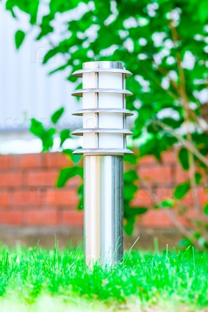 Маленький фонарь в саду на земле