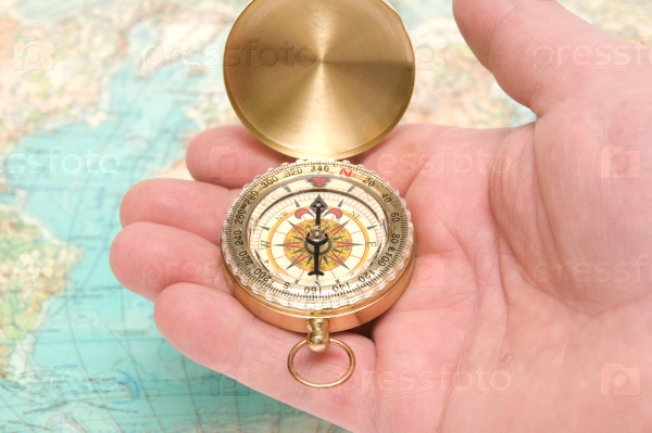 Рука держит компас