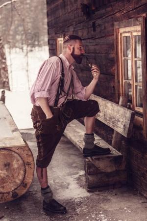 Молодой человек в баварских кожаных штанах с трубкой в руке