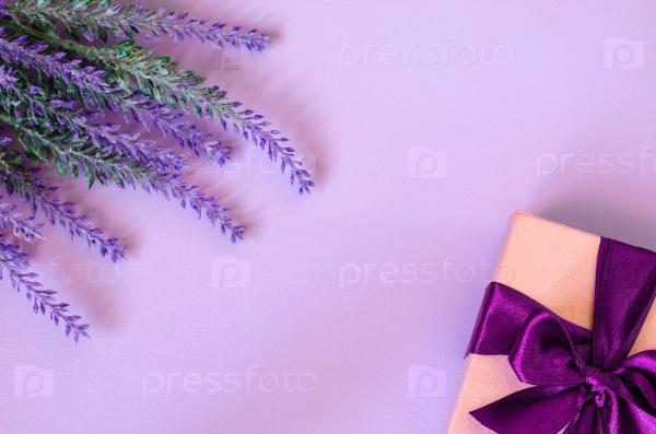 Розовая подарочная коробка и лаванда на фиолетовом фоне