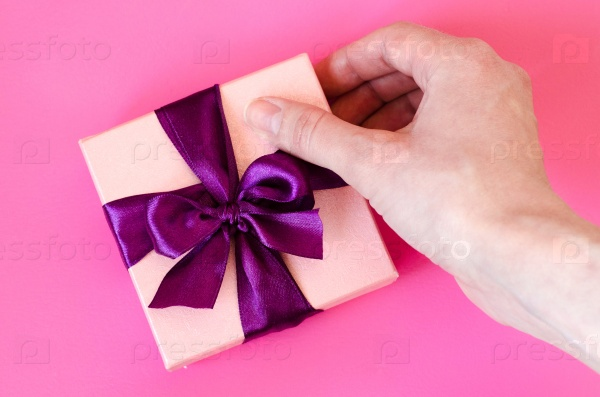 Подарочная коробка в руках женщины на фоне