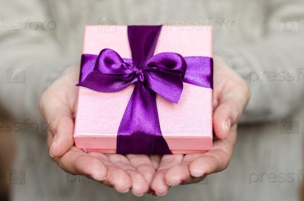 Молодая женщина держит подарок