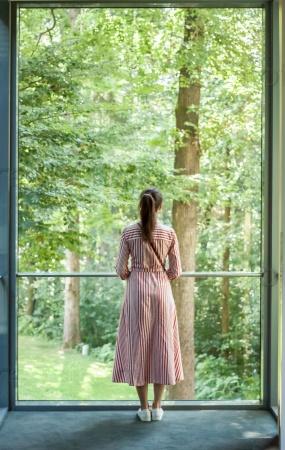 Женщина смотрит в окно на зеленый лес