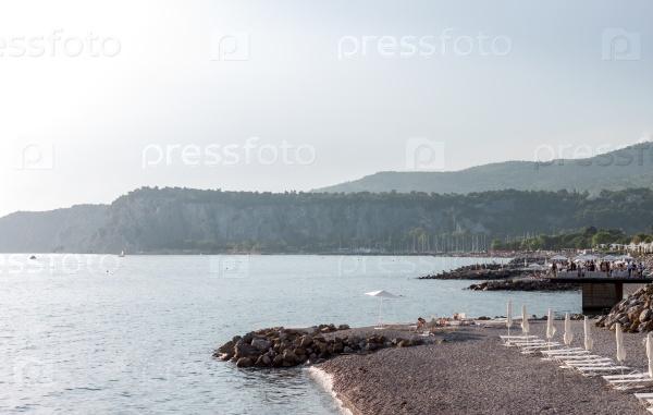 Белые шезлонги на солнечном пляже