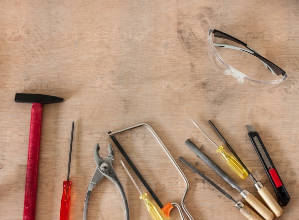 Инструменты в мастерской на деревянном фоне