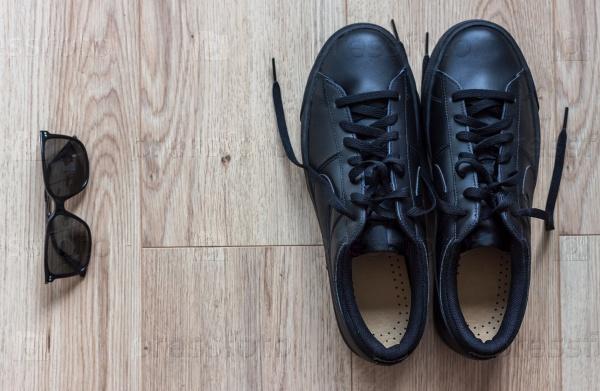 Очки и кроссовки на деревянном фоне