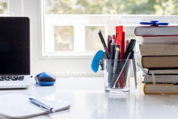 Рабочий стол с канцелярским принадлежностями, ноутбуком и книгами