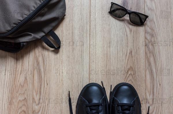 Рюкзак очки и кроссовки на деревянном фоне