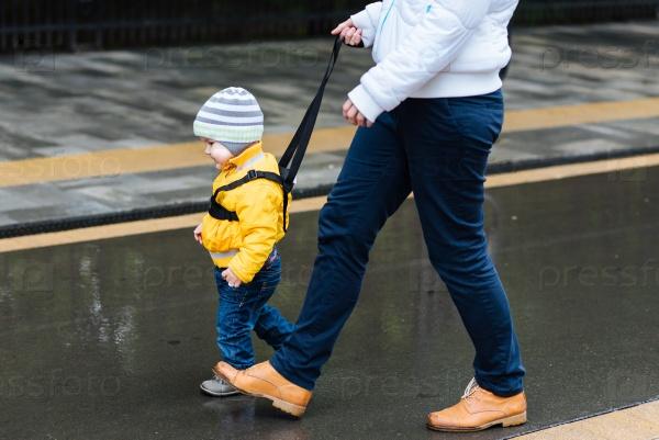 Мама страхует ребенка во время прогулки