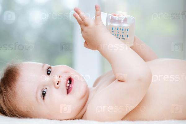 Ребенок пьет компот из бутылки дома