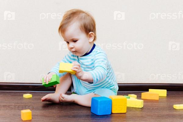 Ребенок играет в кубики, сидя на полу